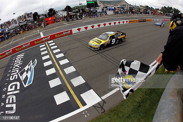 Marcos Ambrose, driver of the Stanley Ford, takes the checkered flag ahead of Brad Keselowski, driver of the Miller Lite Dodge, to win the NASCAR...