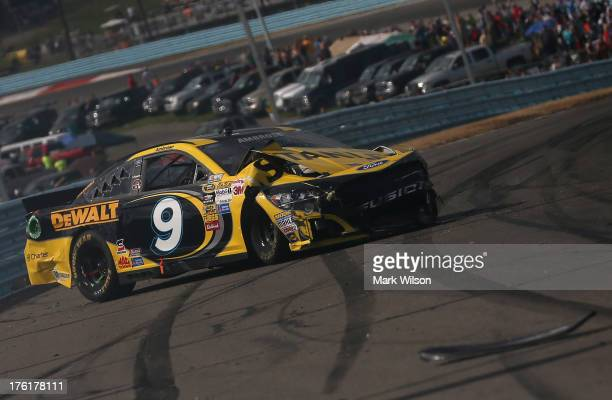 Marcos Ambrose, driver of the Stanley/CTC Jumpstart Ford, sits on the track after an incident during the NASCAR Sprint Cup Series Cheez-It 355 at The...