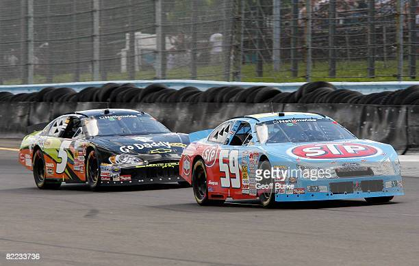 Marcos Ambrose driver of the STP Ford races Dale Earnhardt Jr driver of the Go Daddy Chevrolet during the NASCAR Nationwide Series Zippo 200 at the...