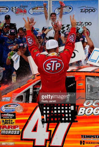 Marcos Ambrose, driver of the STP Toyota, celebrates in victory lane after winning the NASCAR Nationwide Series Zippo 200 at Watkins Glen...