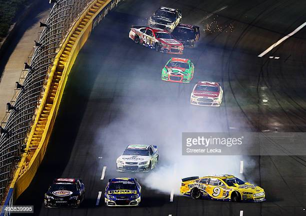 Marcos Ambrose, driver of the Twisted Tea Ford, and Landon Cassill, driver of the HIllman Racing Chevrolet, spin out during the NASCAR Sprint Cup...
