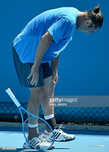 Marcos Bagdatis of Cyprus holds his knee during a practice session ahead of the Australian Open tennis tournament in Melbourne on January 10 2014...