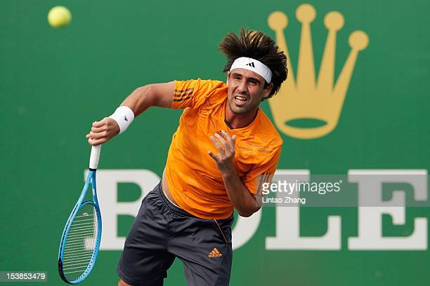 Marcos Baghdatis of Cyprus returns a shot to Milos Raonic of Canada during the day four of Shanghai Rolex Masters at the Qi Zhong Tennis Center on...