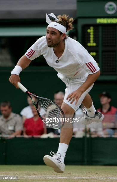 Marcos Baghdatis of Cyprus serves to Lleyton Hewitt of Australia during day nine of the Wimbledon Lawn Tennis Championships at the All England Lawn...