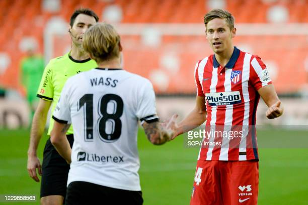 Marcos Llorente of Atletico de Madrid and Daniel Wass of Valencia react during the Spanish La Liga football match between Valencia and Atletico de...