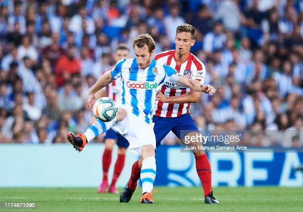 Marcos Llorente of Atletico de Madrid competes for the ball with David Zurutuza of Real Sociedad during the Liga match between Real Sociedad and Club...