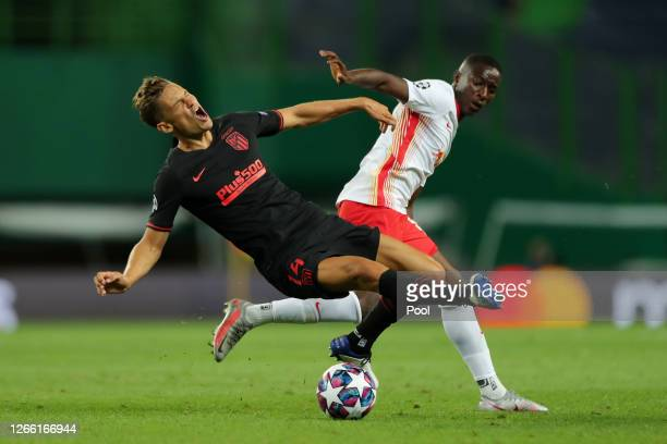 Marcos Llorente of Atletico de Madrid is challenged by Amadou Haidara of RB Leipzig during the UEFA Champions League Quarter Final match between RB...