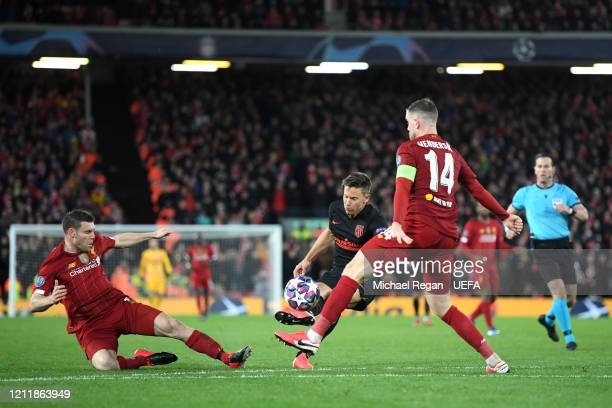 Marcos Llorente of Atletico Madrid scores his team's second goal while under pressure from James Milner and Jordan Henderson of Liverpool during the...