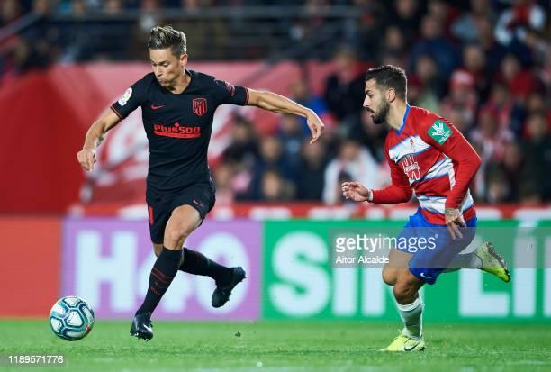 Marcos Llorente of Club Atletico de Madrid duels for the ball with Alvaro Vadillo of Granada CF during the Liga match between Granada CF and Club...