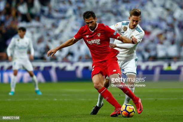 Marcos Llorente of Real Madrid CF competes for the ball with Franco Vazquez of Sevilla FC during the La Liga match between Real Madrid CF and Sevilla...