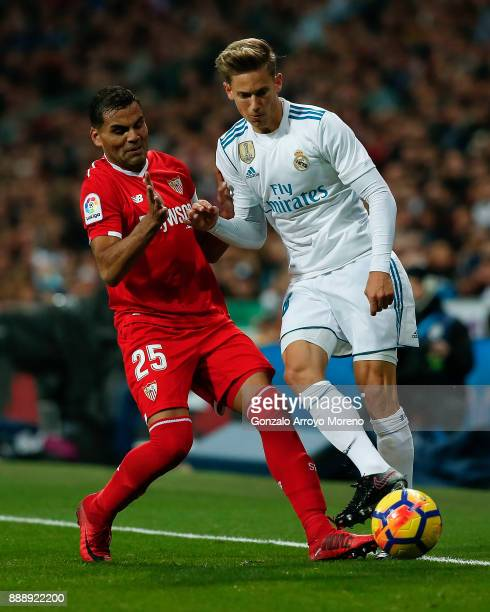 Marcos Llorente of Real Madrid CF competes for the ball with Gabriel Mercado of Sevilla FC during the La Liga match between Real Madrid CF and...