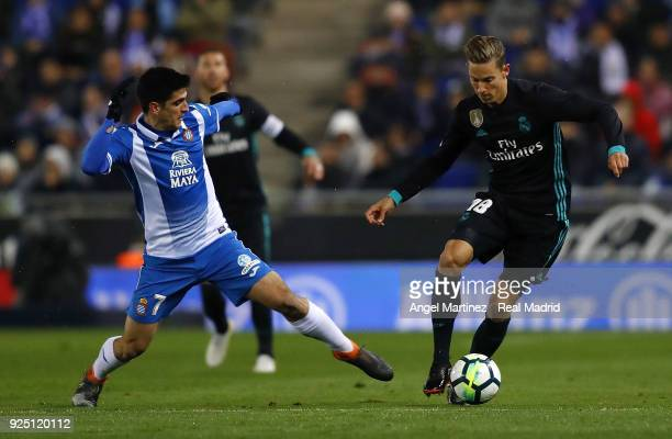 Marcos Llorente of Real Madrid competes for the ball with Gerard Moreno of Espanyol during the La Liga match between Espanyol and Real Madrid at RCDE...
