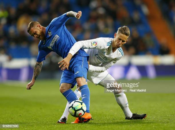 Marcos Llorente of Real Madrid competes for the ball with Vitorino Antunes of Getafe during the La Liga match between Real Madrid and Getafe at...