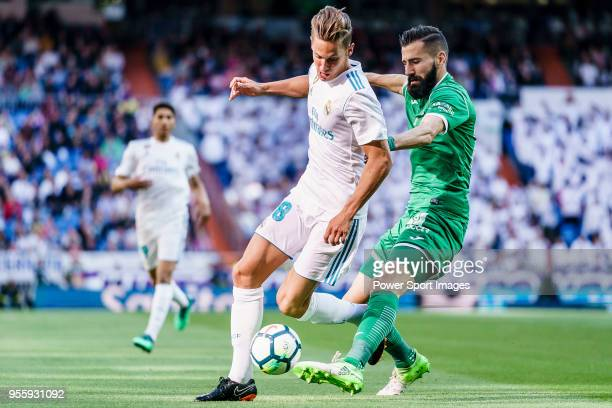 Marcos Llorente of Real Madrid fights for the ball with Dimitrios Siovas of CD Leganes during the La Liga 201718 match between Real Madrid and CD...