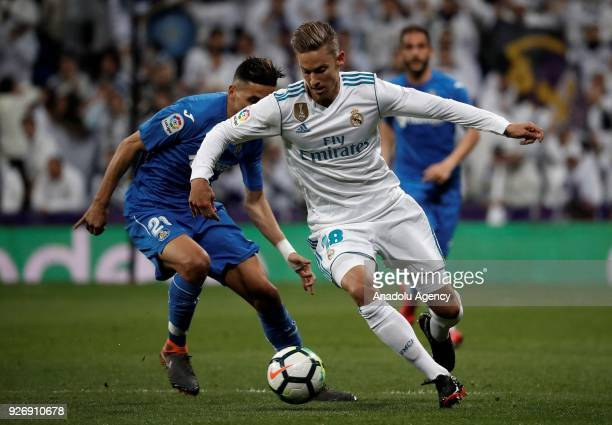 Marcos Llorente of Real Madrid in action against Faycal Fajr of Getafe during the La Liga soccer match between Real Madrid and Getafe at Santiago...