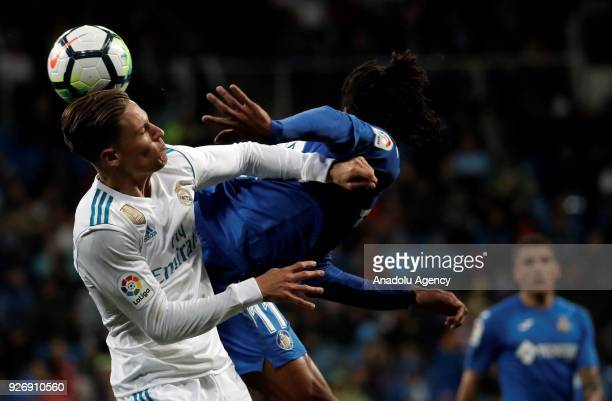 Marcos Llorente of Real Madrid in action against Loic Remy of Getafe during the La Liga soccer match between Real Madrid and Getafe at Santiago...