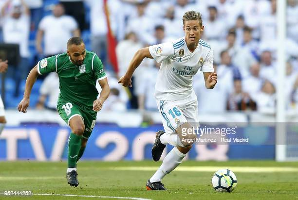Marcos Llorente of Real Madrid is chased by Nabil El Zhar of Leganes during the La Liga match between Real Madrid and Leganes at Estadio Santiago...