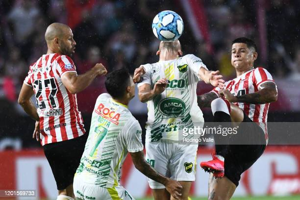 Marcos Rojo and Javier Mascherano of Estudiantes fight for the ball with Ruben Botta and Juan Rodriguez of Defensa y Justicia during a match between...