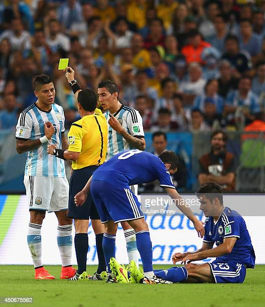 Marcos Rojo of Argentina is shown a yellow card by referee Joel Aguilar as Miralem Pjanic of Bosnia and Herzegovina helps teammate Mensur Mujdza...