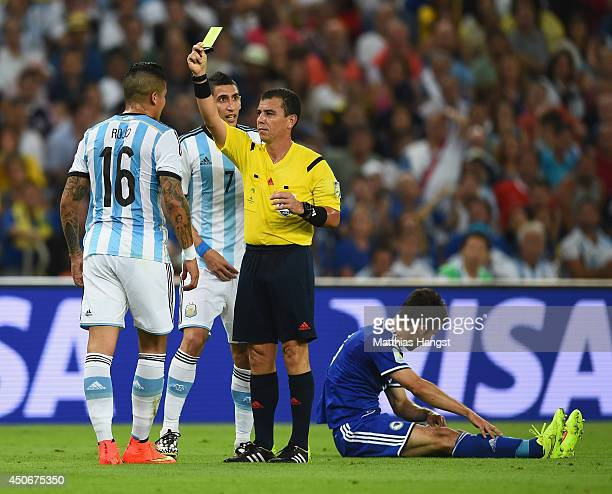 Marcos Rojo of Argentina is shown a yellow card by referee Joel Aguilar during the 2014 FIFA World Cup Brazil Group F match between Argentina and...