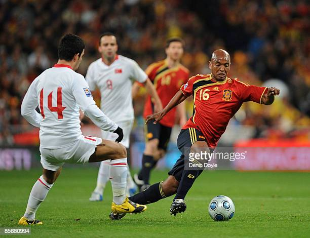 Marcos Senna of Spain gets past Arda Turan of Turkey during the FIFA2010 World Cup Qualifier match between Spain and Turkey at the Estadio Santiago...