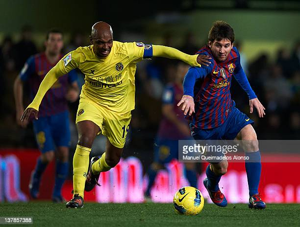 Marcos Senna of Villarreal competes for the ball with Lionel Messi of Barcelona during the la Liga match between Villarreal and Barcelona at El...