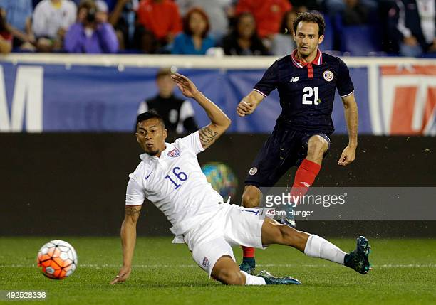 Marcos Urena of Costa Rica takes a shot defended by Michael Orozco of the United States during the first half at Red Bull Arena on October 13 2015 in...