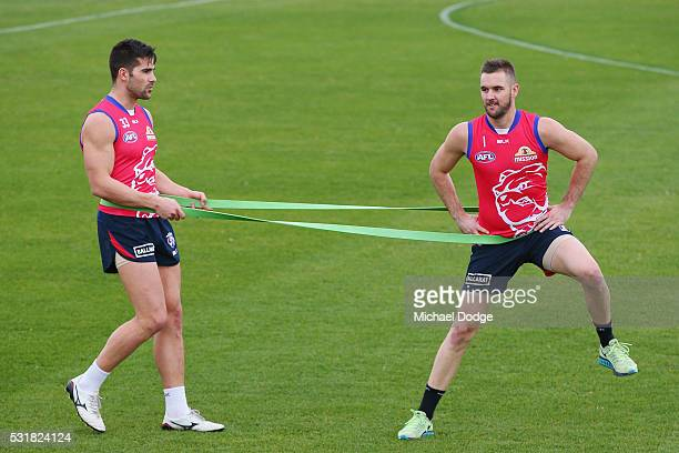 Marcus Adams of the Bulldogs holds a band to provide resistance for Matt Suckling during a Western Bulldogs AFL training session at Whitten Oval on...