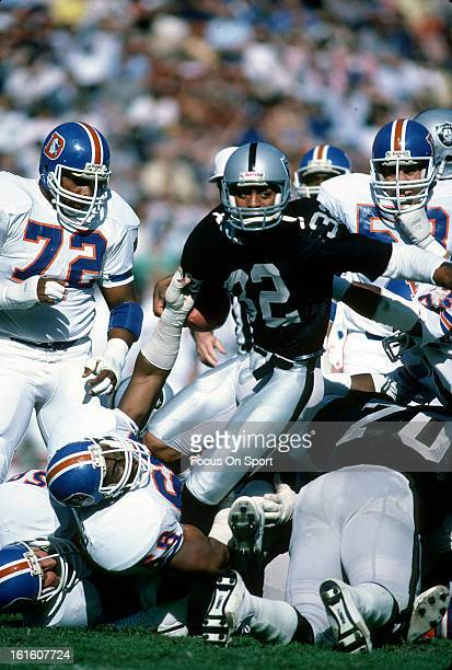 Marcus Allen of the Los Angeles Raiders carries the ball against the Denver Broncos during an NFL football game November 13 1983 at the Los Angeles...