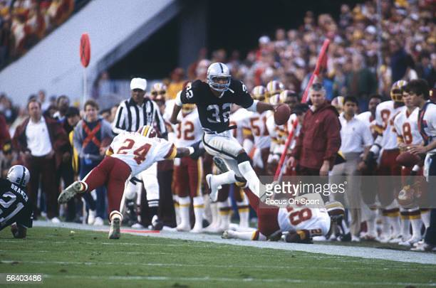 Marcus Allen of the Los Angeles Raiders carries the ball against the Washington Redskins during Super Bowl XVIII at Tampa Stadium on January 22 1984...