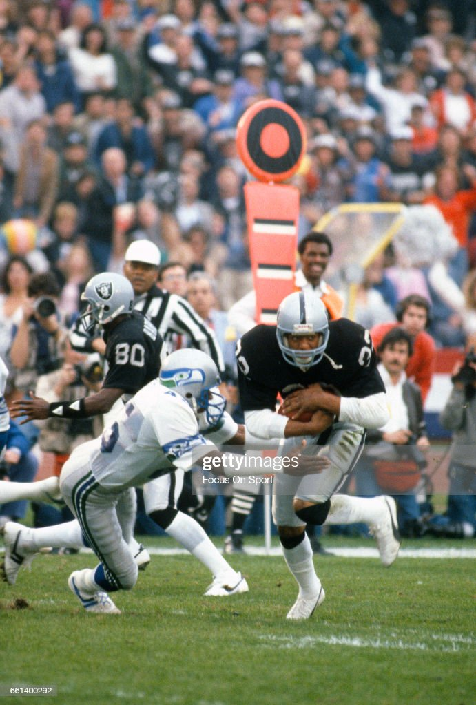 Marcus Allen of the Los Angeles Raiders carries the ball against the Seattle Seahawks during the AFC Conference Championship game January 8 1984 at...
