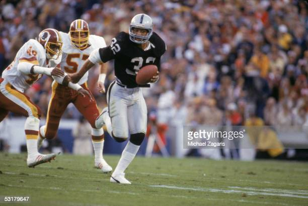 Marcus Allen of the Los Angeles Raiders carries the ball during the Superbowl XVIII game against the Washington Redskins on January 221984 Tampa...