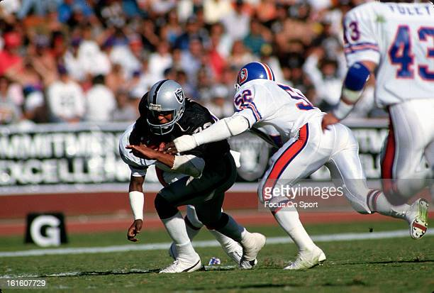 Marcus Allen of the Los Angeles Raiders gets tackled by Ken Woodard of the Denver Broncos during an NFL football game November 13 1983 at the Los...