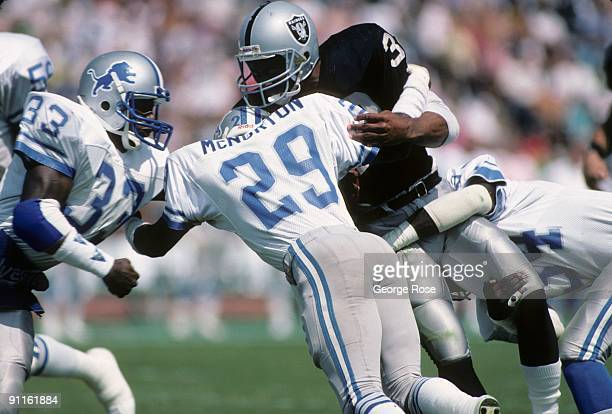 Marcus Allen of the Los Angeles Raiders runs the ball against Bruce McNorton and William Graham of the New England Patriots during the game at the...