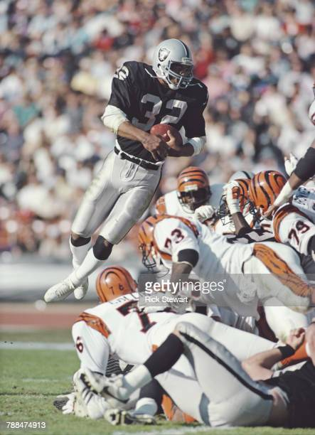 Marcus Allen Running Back for the Los Angeles Raiders climbs over the Cincinnati Bengals defense during their American Football Conference West game...