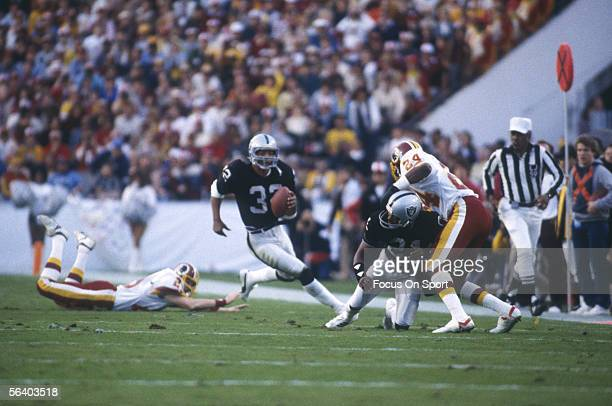Marcus Allen running back for the Oakland Raiders carries the ball for yardage while surrounded by Washington Redskins during Super Bowl XVIII at...