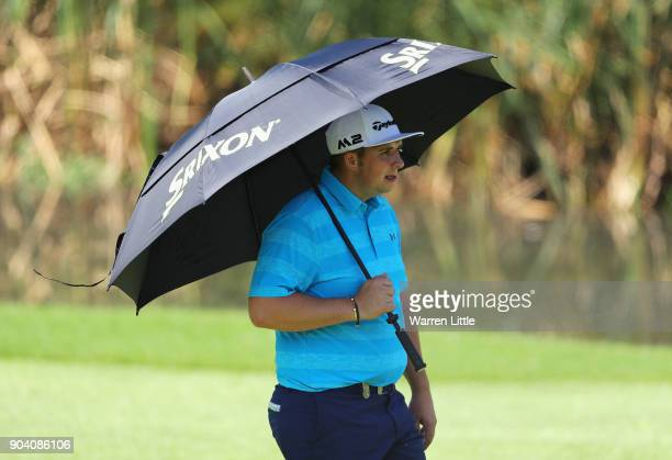 Marcus Armitage of England uses an umbrella to protect himself from the sun on the 3rd hole during day two of the BMW South African Open Championship...