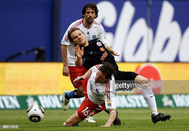 Marcus Berg and Ruud van Nistelrooy of Hamburg as well as Eugen Polanski of Mainz compete for the ball during the Bundesliga match between Hamburger...