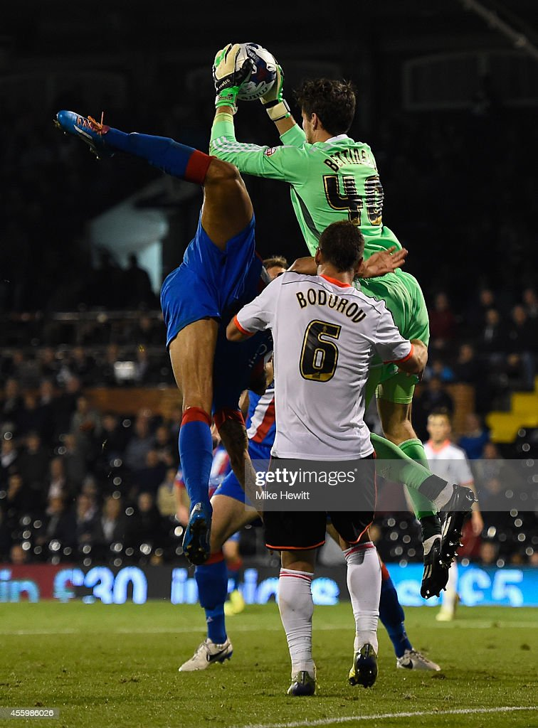 Marcus Bettinelli of Fulham catches the ball as Nathan Tyson of Doncaster falls awkwardly during the Capital One Cup Third Round match between Fulham and Doncaster Rovers at Craven Cottage on September 23, 2014 in London, England.