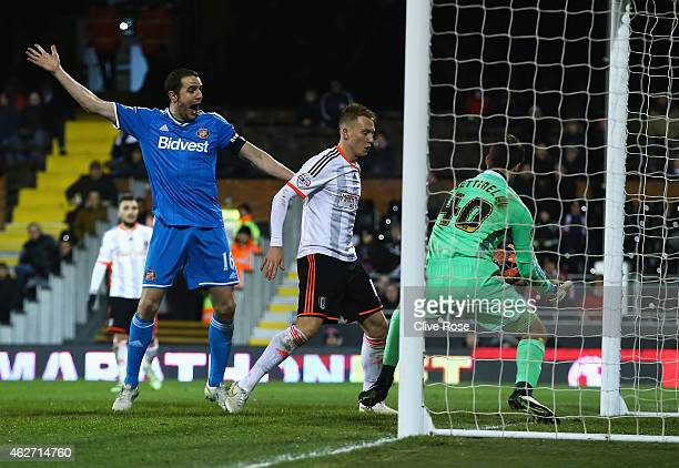 Marcus Bettinelli of Fulham fumbles the ball in to his own net for Sunderland's opening goal as John O'Shea of Sunderland celebrates during the FA...