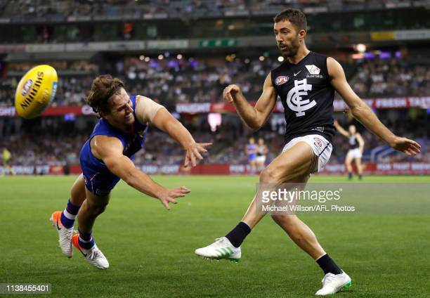 Marcus Bontempelli of the Bulldogs attempts to smother the kick of Kade Simpson of the Blues during the 2019 AFL round 05 match between the Western...