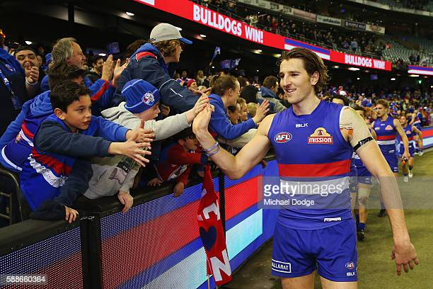 Marcus Bontempelli of the Bulldogs celebrates the win with fans during the round 21 AFL match between the Western Bulldogs and the Collingwood...
