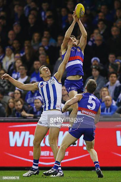 Marcus Bontempelli of the Bulldogs competes for the ball over Drew Petrie of the Kangaroos during the round 20 AFL match between the Western Bulldogs...