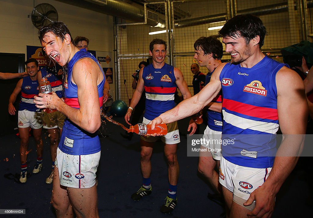 Marcus Bontempelli of the Bulldogs gets doused with Gatorade by Easton Wood of the Bulldogs as they celebrate their win during the round 13 AFL match between the Collingwood Magpies and the Western Bulldogs at Etihad Stadium on June 15, 2014 in Melbourne, Australia.