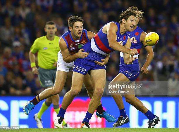 Marcus Bontempelli of the Bulldogs handballs whilst being tackled by Ryan Bastinac of the Lions during the round five AFL match between the Western...