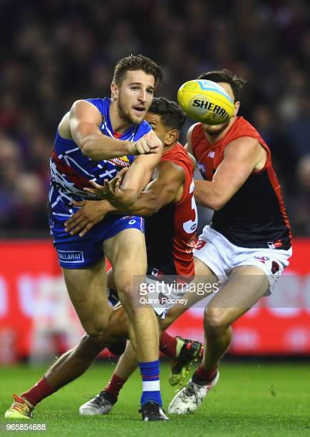 Marcus Bontempelli of the Bulldogs handballs whilst being tackled by Neville Jetta of the Demons during the round 11 AFL match between the Western...