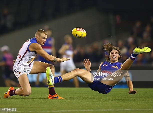 Marcus Bontempelli of the Bulldogs is challenged by Mitch Robinson of the Lions during the round 12 AFL match between the Western Bulldogs and the...