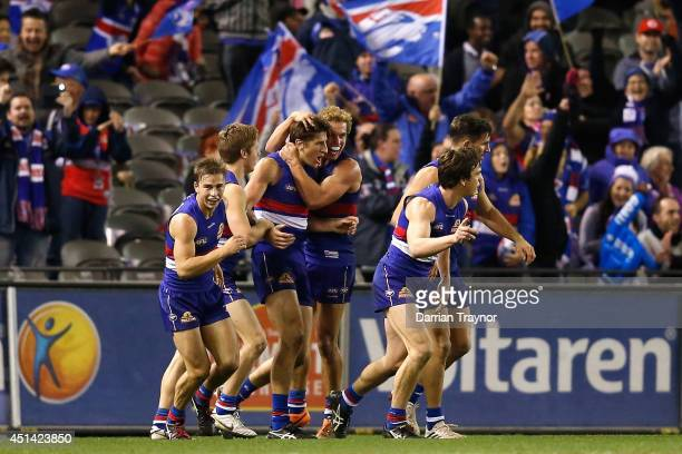 Marcus Bontempelli of the Bulldogs is congratulated by team mates after kicking the winning goal during the round 15 AFL match between the Western...