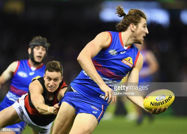 Marcus Bontempelli of the Bulldogs is tackled by Orazio Fantasia of the Bombers during the round 19 AFL match between the Western Bulldogs and the...