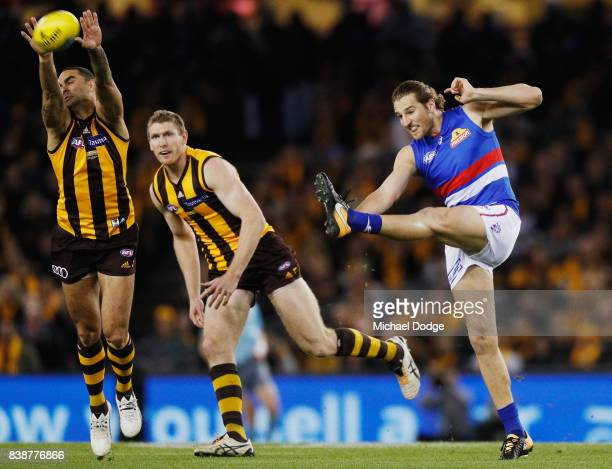 Marcus Bontempelli of the Bulldogs kicks the ball Shaun Burgoyne of the Hawks during round 23 AFL match between the Hawthorn Hawks and the Western...